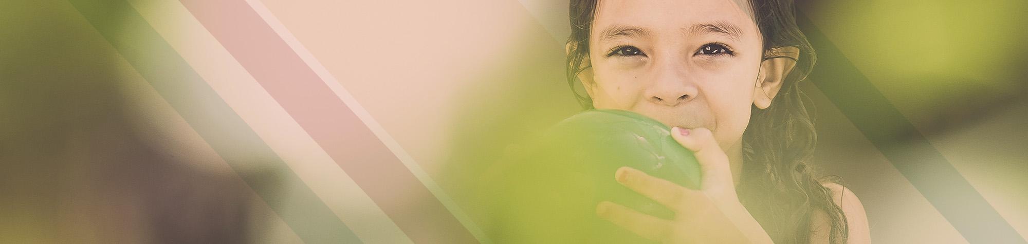 Kind mit gruenem Ball in den Haenden