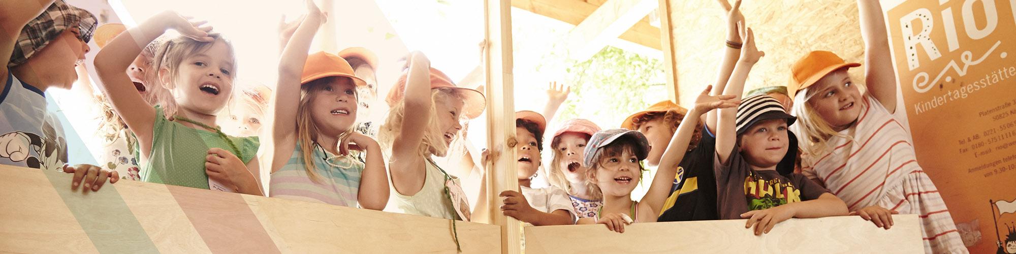 Viele Kinder mit Kappen heben die Haende und lachen